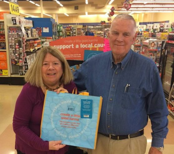 Executive Director and Board President display Hannaford Helps bag